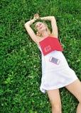 Reizvolle junge blonde Frau, die im Gras lacht Lizenzfreie Stockfotografie