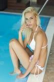 Reizvolle junge blonde Frau im Bikini durch das Pool Lizenzfreie Stockbilder