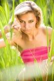 Reizvolle junge blonde Frau im grünen Gras Lizenzfreie Stockbilder