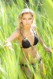 Reizvolle junge blonde Frau im schwarzen Bikini Stockfoto