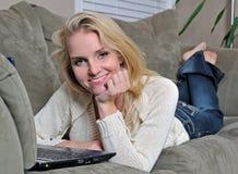 Reizvolle junge Frau auf Couch mit Laptop Lizenzfreies Stockfoto