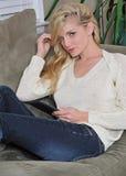 Reizvolle junge Frau auf Couch mit Tablette Stockbilder