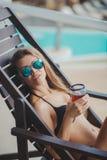 Reizvolle junge Frau, die auf Klappstuhl sich entspannt Lizenzfreies Stockfoto