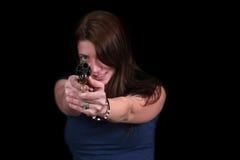 Reizvolle junge Frau, die Gewehr auf Kamera abzielt Lizenzfreies Stockbild