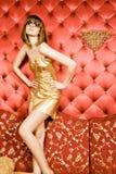 Reizvolle junge Frau im goldenen Kleid und in den Gläsern Stockfotografie