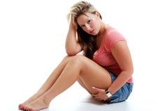 Reizvolle junge Frau mit kurzem Rock und rosafarbener Oberseite Stockfotos