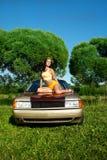 Reizvolle junge Frau sitzen auf Retro- Auto lizenzfreies stockbild