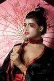 Reizvolle junge Geisha, die einen Regenschirm anhält Stockfotografie