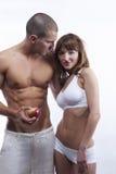 Reizvolle junge Paare im Weiß, mit Apfel Stockfotografie