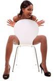 Reizvolle junge schwarze Frau, die im Stuhl aufwirft stockfotos