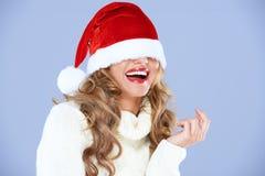 Reizvolle lächelnde Frau blind gemacht durch roten Sankt-Hut Lizenzfreies Stockfoto