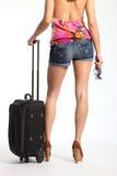 Reizvolle lange Fahrwerkbeine der Frau wartend mit Koffer Stockfoto