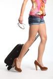 Reizvolle lange Fahrwerkbeine, die am Feiertag mit Koffer gehen Lizenzfreie Stockfotografie