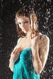 Reizvolle Mädchenhaltung im Kleid unter Regen Stockbild