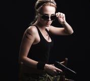 Reizvolle Militärfrau, die mit Gewehr aufwirft Stockbild