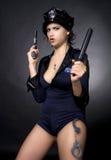 Reizvolle Polizeifrau, die eine Gewehr anhält Stockfoto