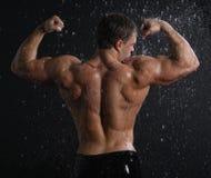 Reizvolle Rückseite des jungen Mannes des nassen Muskels unter dem Regen Stockfoto
