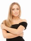 Reizvolle schöne blonde Frau im schwarzen Kleid Stockbild