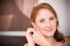 Reizvolle schöne Braut, die ihre Ohrringe einsteckt Lizenzfreies Stockfoto