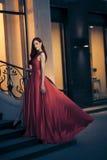 Reizvolle Schönheitsfrau in flatterndem rotem Kleid Lizenzfreies Stockfoto