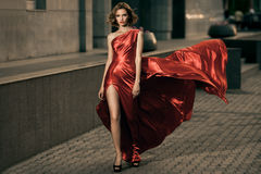 Reizvolle Schönheitsfrau in flatterndem rotem Kleid Lizenzfreie Stockbilder