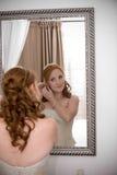 Reizvolle schöne Braut, die ihre Ohrringe einsteckt Lizenzfreie Stockfotografie