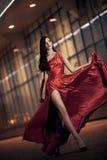Reizvolle Schönheitsfrau in flatterndem rotem Kleid Lizenzfreie Stockfotografie