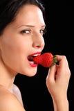 Reizvoller Blick durch die Frau, die frische Erdbeerefrucht isst Stockbild