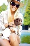 Reizvoller blonder Frauen-Holding-Hund Stockfoto