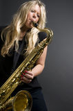 Reizvoller blonder weiblicher Saxophonspielermusiker Stockbild