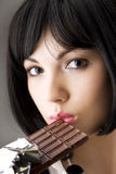 Reizvoller Brunette, der Schokolade isst Stockbilder
