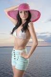 Reizvoller Brunette mit Kurzschlüssen, Hut und der Hand auf der Hüfte Stockfotografie