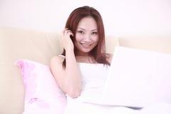Reizvoller Frauengebrauchlaptop auf Bett Lizenzfreies Stockfoto