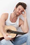 Reizvoller Gitarrenspieler, der zum Musiklächeln hört Lizenzfreie Stockfotos
