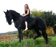 Reizvoller Jugendlicher und ihr schwarzer Stallion Stockbilder
