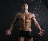 Reizvoller junger Mann des nassen Muskels, der unter dem Regen aufwirft Lizenzfreies Stockbild