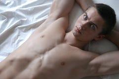 Reizvoller Mann auf dem Bett Stockbilder