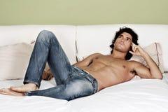 Reizvoller mit nacktem Oberkörper junger Mann auf Bett Stockfoto