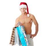 Reizvoller muskulöser mit nacktem Oberkörper Mann im Weihnachtsmann-Hut Lizenzfreie Stockbilder