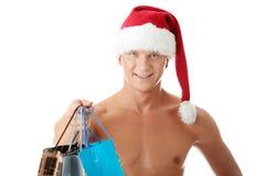 Reizvoller muskulöser mit nacktem Oberkörper Mann im Weihnachtsmann-Hut Lizenzfreies Stockfoto
