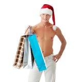 Reizvoller muskulöser mit nacktem Oberkörper Mann im Weihnachtsmann-Hut Stockfotografie
