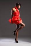 Reizvolles Art und Weisebaumuster, das kurzes rotes Kleid trägt Stockfotografie