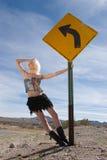 Reizvolles blondes Art und Weisemädchen durch Verkehrsschild Stockbild