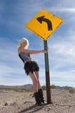 Reizvolles blondes Art und Weisemädchen durch Verkehrsschild Lizenzfreie Stockfotografie