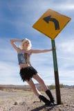 Reizvolles blondes Art und Weisemädchen durch Verkehrsschild Lizenzfreies Stockbild