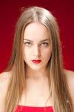 Reizvolles blondes auf rotem Hintergrund Stockfotografie