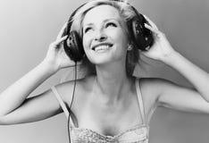 Reizvolles blondes Baumuster hört Musik Stockbild