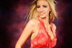 Reizvolles blondes Frauenart und weisebaumuster im roten Kleid Stockfoto