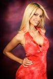 Reizvolles blondes Frauenart und weisebaumuster im roten Kleid Lizenzfreies Stockbild