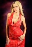 Reizvolles blondes Frauenart und weisebaumuster im roten Kleid Stockfotografie